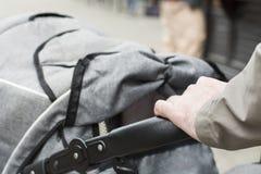 Man& x27; рука s на детской дорожной коляске Стоковая Фотография RF