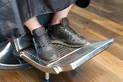 Man& x27; 在理发椅的s腿 免版税库存照片