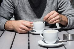 Man& x27; 搅动在一个加奶咖啡杯子的s手热的咖啡在酒吧户外 库存照片