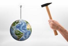 Man& x27 ; main de s conduisant le clou dans le mur avec la terre hunging là-dessus Image libre de droits