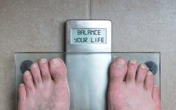 Man& x27; os pés de s na escala do peso - equilibre sua vida Fotografia de Stock Royalty Free