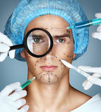 Man's face and beautician hands with syringes and scalpels near his face. Stock Photo