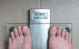 Man& x27;s feet on weight scale - Balance your life Royalty Free Stock Photography