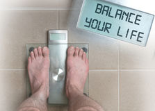 Man& x27;s feet on weight scale - Balance your life Royalty Free Stock Images