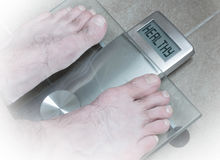 Man& x27;s feet on weight scale - Balance your life Royalty Free Stock Image