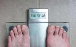 Man& x27;s feet on weight scale - Time for gym Stock Photography