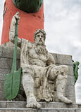 A man's figure with a paddle sitting at the foot of the rostrum column on the Spit of Vasilievsky Island. Royalty Free Stock Photos