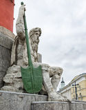 A man's figure with a paddle sitting at the foot of the rostrum column on the Spit of Vasilievsky Island. Royalty Free Stock Images