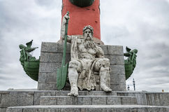 A man's figure with two rostra sitting at the foot of the rostrum column on the Spit of Vasilievsky Island. Royalty Free Stock Photo