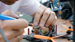 Man& x27; s-händer som svetsar detaljer som monterar FPV-surret Arkivbild