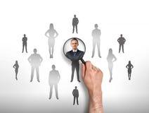 Man& x27; s hand concentreren meer magnifier zich op zakenman Stock Afbeelding