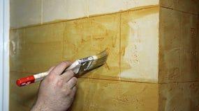 Man& x27; s-Hand, die eine Wand mit Pinsel malt Stockbild