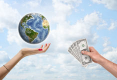 Man's hand giving dollar bills to female, which supports the planet Earth. Royalty Free Stock Photography