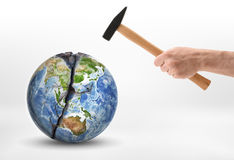 Man's hand with a hammer hits the planet Earth. Stock Image