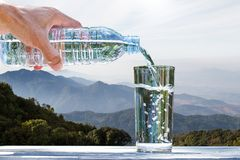 Man& x27;s hand holding drinking bottle water and pouring water into Royalty Free Stock Image