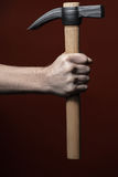 Man's hand holding hammer on red background Royalty Free Stock Images