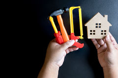 Man& x27;s hand holding wooden house toy and construction tools toy o Royalty Free Stock Images