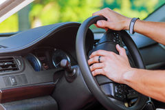 Man's hand on the steering wheel of a car Stock Image