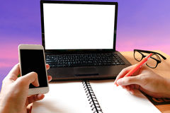 A man's hand using mock up laptop and writing note, holding smar Royalty Free Stock Photography