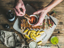 Man' s hands dipping piece of roasted pork to ketchup Stock Photos