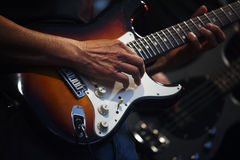 Man& x27;s hands playing on an electric guitar in a band on stage, en Royalty Free Stock Images