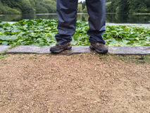 Man's legs wearing waterproof trousers and walking boots. Stock Photos