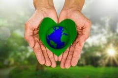 Man& x27 ; s remet tenir la feuille verte en forme de coeur avec la terre sur le fond brouillé de nature Image libre de droits