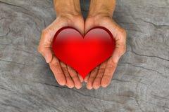 Man& x27 ; s remet tenir le coeur rouge sur le backgro en bois brouillé de vintage Photo libre de droits