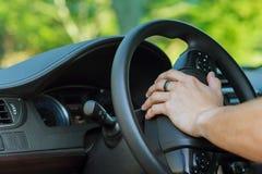 Man& x27; s ręka na kierownicie samochód Fotografia Stock