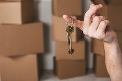 Man& x27; s ręka trzyma klucze twój nowy domowy zakończenie Obraz Stock