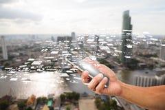 Man& x27; s smartphone van de handholding met bedrijfspictogram op vage stadsachtergrond Stock Fotografie