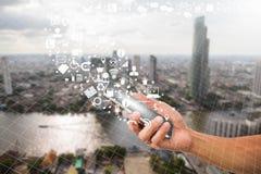 Man& x27; s smartphone van de handholding met bedrijfspictogram op vage stadsachtergrond Royalty-vrije Stock Afbeeldingen