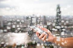 Man& x27; s smartphone van de handholding met gezoem vertroebelde bedrijfspictogram op vage stadsachtergrond Royalty-vrije Stock Afbeeldingen