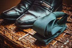 Man's Black Leather Shoes Near to Green and White Spotted Tie Stock Photography