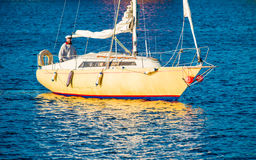 Man in yacht. Happy beard man in yellow yacht. Blue water, reflection stock images