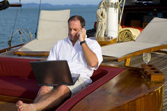 Man on yacht with phone and laptop Stock Images