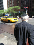 Man With Yamulka on Street. Waiting to cross the street in NYC with cab driving by royalty free stock image