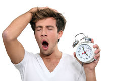 A man yawning. Man an alarm clock yawning royalty free stock photos