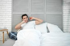 Man yawning in the bed. Caucasian man wearing pijama yawning in the bed at the morning royalty free stock photography