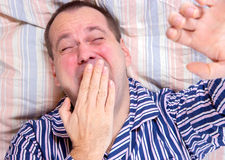 Man yawning in bed Stock Images