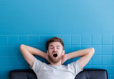 Man yawning and going asleep in his living room. The man yawning and going asleep in his living room Stock Photography