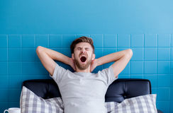 Man yawning and going asleep. Man yawning and going asleep in his living room Royalty Free Stock Images