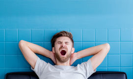 Man yawning and going asleep in his living room. The man yawning and going asleep in his living room Royalty Free Stock Images