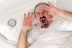 Man yawning loudly resting in bed Stock Photo