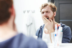 Man yawning. Messy yawning man standing in front of mirror in the morning Royalty Free Stock Photography