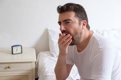 Man yawning. He is sitting on the edge of a bed in the morning Stock Images