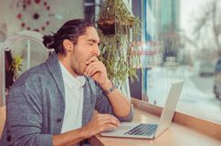 Man yawning sleepy in front of the laptop stock images