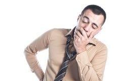 Man yawning. Young businessman yawning, isolated on white background. Close up studio shot royalty free stock image