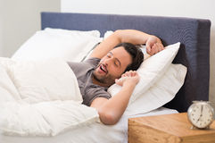 Man yawns in bed. Young man stretching while waking up in the morning. Man yawning while waking up. Lazy young man in sleep. Portrait of latin man yawns and Royalty Free Stock Images