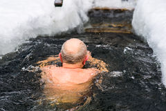 A man in years swims in the ice hole Royalty Free Stock Images